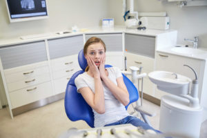 people, medicine, stomatology and phobia concept - scared and terrified patient girl at dental clinic office
