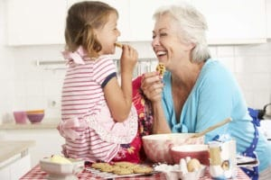 Grandmother And Granddaughter Baking In Kitchen